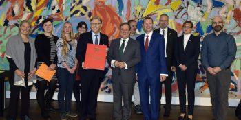 WHKT-Präsident Hans Hund (vorne l.) und WHKT-Hauptgeschäftsführer Reiner Nolten (vorne r.) überreichen Ministerpräsident Armin Laschet (vorne m.) das »Goldene Landesbuch von NRW«.